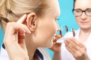 young woman trying on hearing aids
