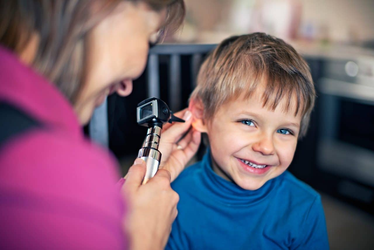 Young boy getting his ears checked by a doctor