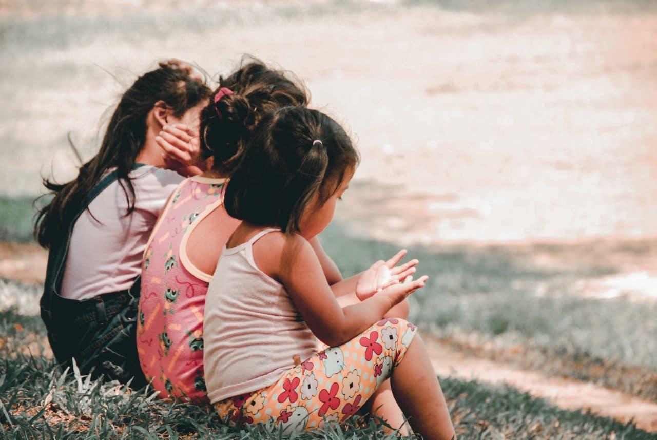 Children sitting together outside.