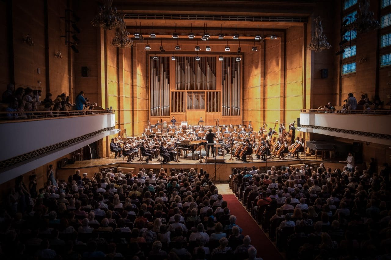 A packed concert venue with a symphony orchestra playing.